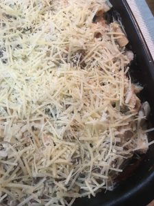 chicken tetrazzini topped with cheese and ready to go in the oven